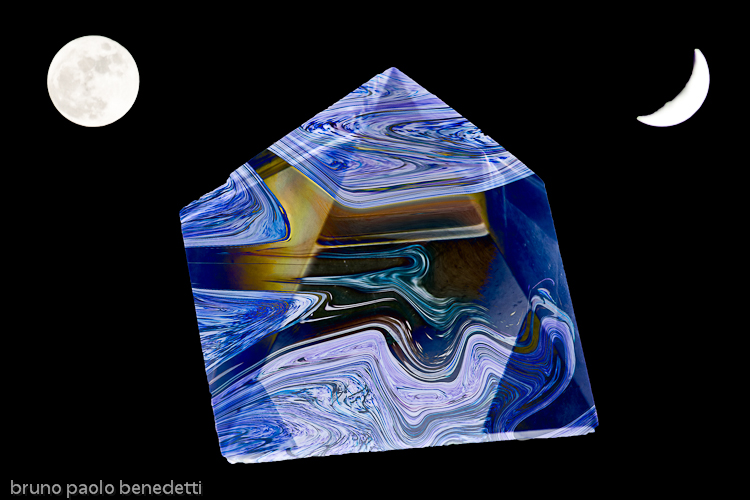 a mottled blue crystal pyramid floating in black space