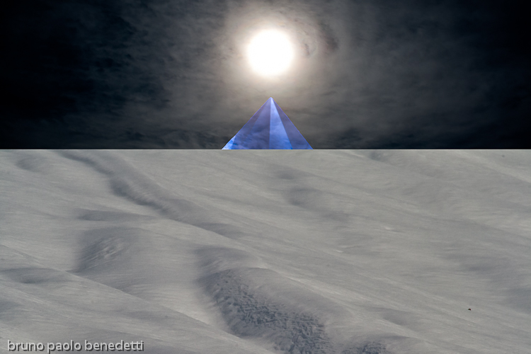 wihte snow and blue pyramid with sun above peak in surreal landscape